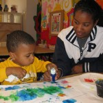 Teen volunteer Cameron works with Wilson on his painting