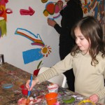 Youth artist Abby picking out colors for the mural with mom, Lisa already busy at work