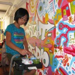 Miya adds her funky eyeball designs to our mural