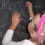 Emerson adds her art to our chalkboard wall.