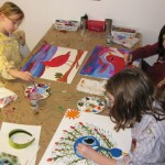 Youth Artists Evelyn, Sofia and Hannah working with acrylic paint on canvas board.