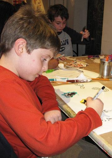 "Youth artist Adam participates in a ""$5 Fridays"" workshop"