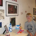 Matthew stands next to his phoenix drawing at the &quot;Art in the Air&quot; youth art show May 2011
