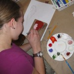 Vivienne works on a portrait with acrylic paint on wood influenced by Chicago Artist Deva Suckerman, as part of the Artist Inspired Workshops at &quot;the Candy Store&quot; Pop-Up Gallery