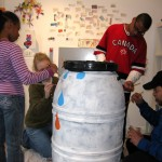 "The Taylor family works with Art Mentor Mindy Fisher on ""It's Raining cats and Dogs"" rain barrel."