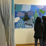 Youth artist Miya shows and mom admire the mural.